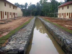 23. Complete row houses. Note the finished drain work. The team cleared the creek for a kilometre to complete this drain